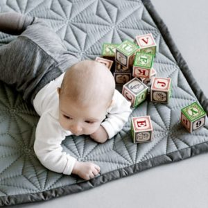 Baby playing on mint colour quilt