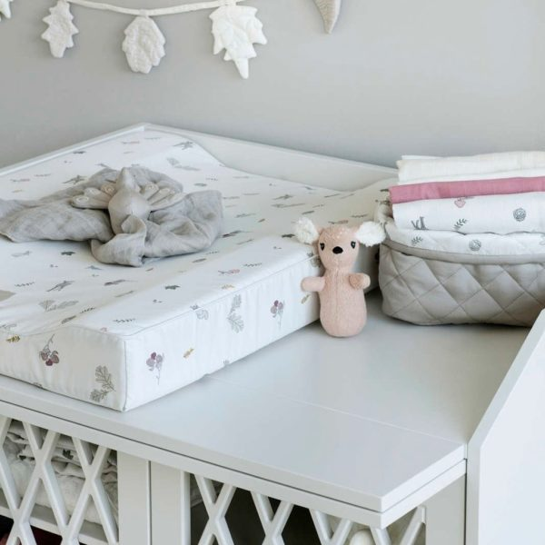 Change table with a changing mat with quilted storage basket with muslin wraps inside