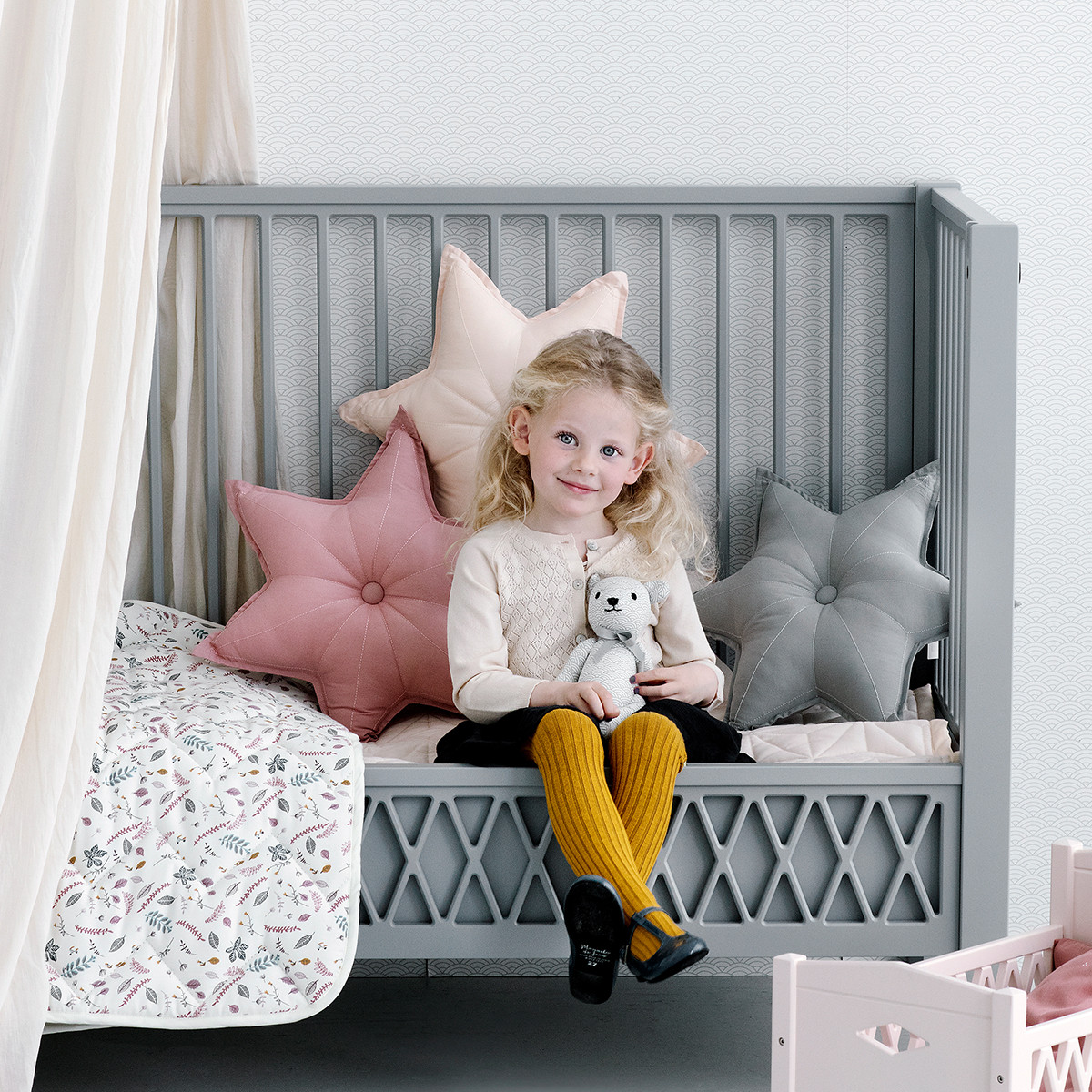 Child in nursery featuring star shaped cushion in old rose
