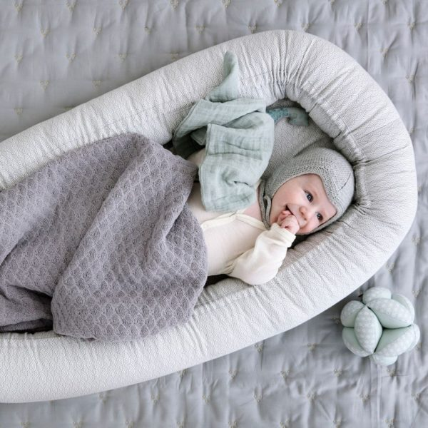 Swaddled baby in nursery nest in grey wave pattern