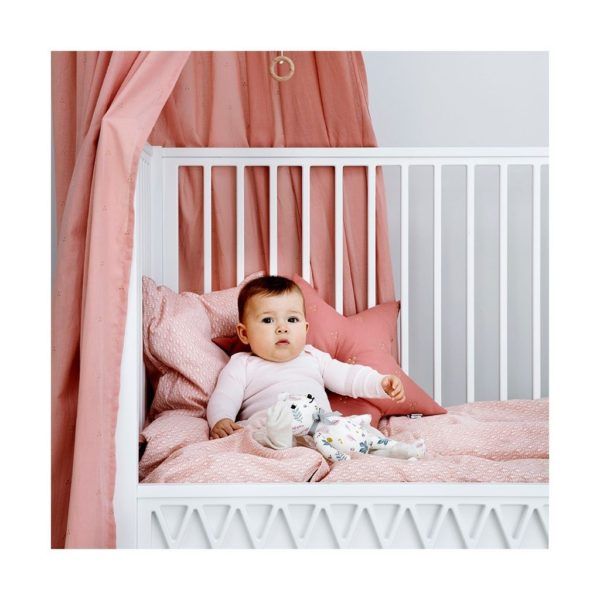 Baby in nursery featuring bed canopy in dot old rose