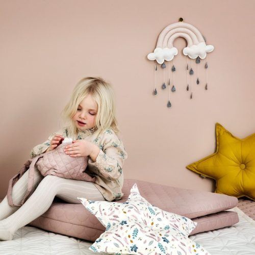Child playing in nursery featuring decorative star cushions