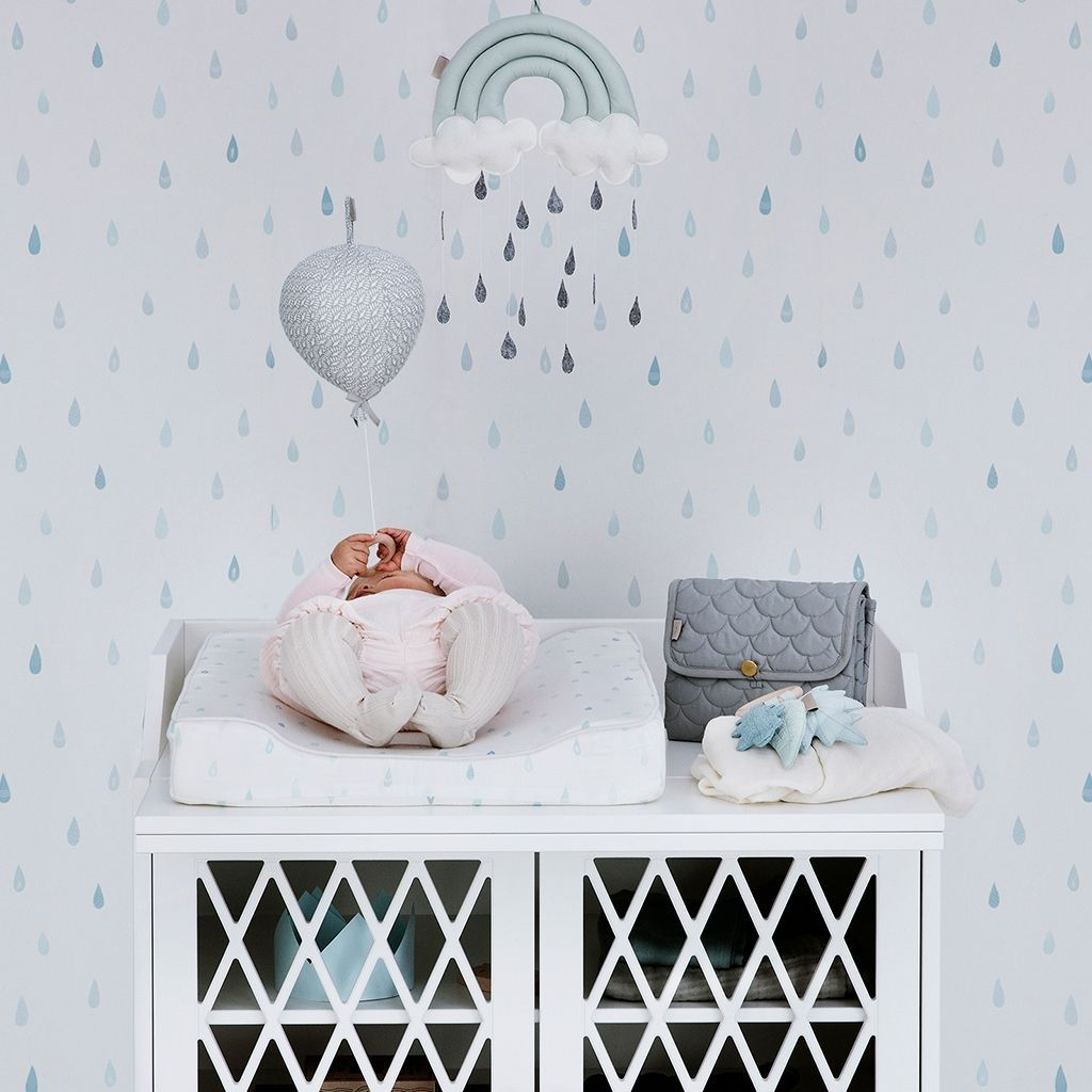 Nursery featuring changing cushion in raindrops pattern