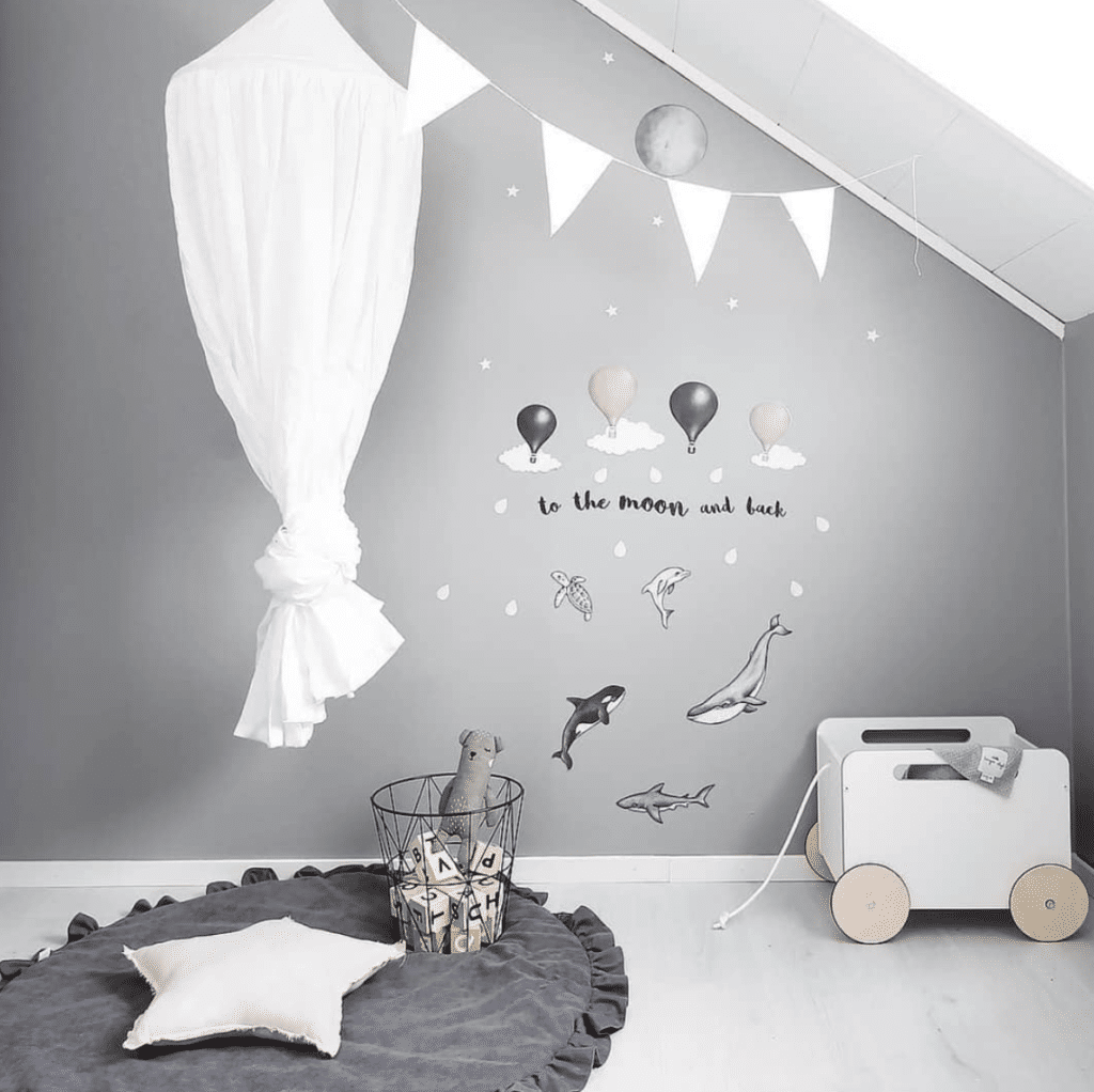 Creme cot canopy in play corner with toys wall stickers and star cushion