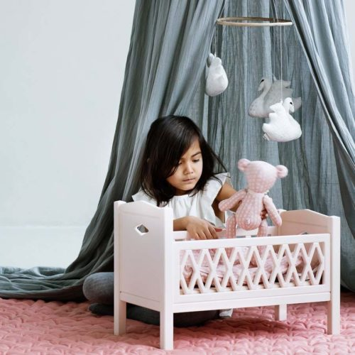 Child in nursery playing with harlequin dolls bed in rose