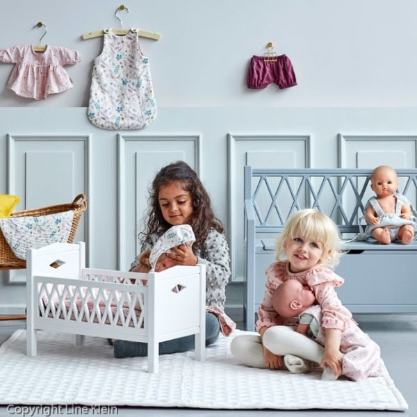 Children in nursery with toys dolls bed and dolls carrier in grey wave