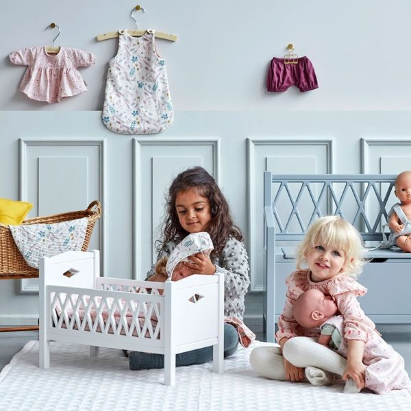 Children in nursery with dolls bed and clothing set in fleur pink