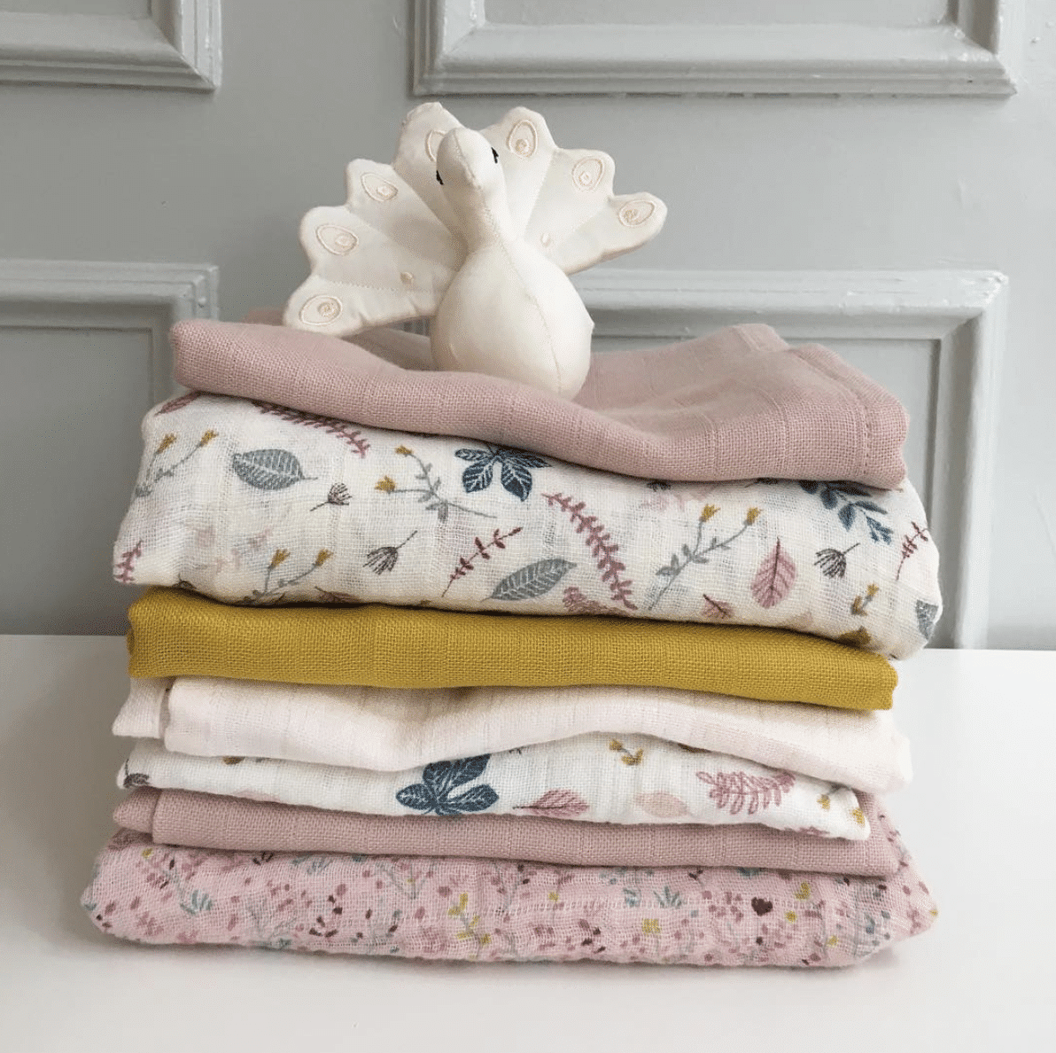Stack of organic muslin wraps in prints and colours by Cam Cam