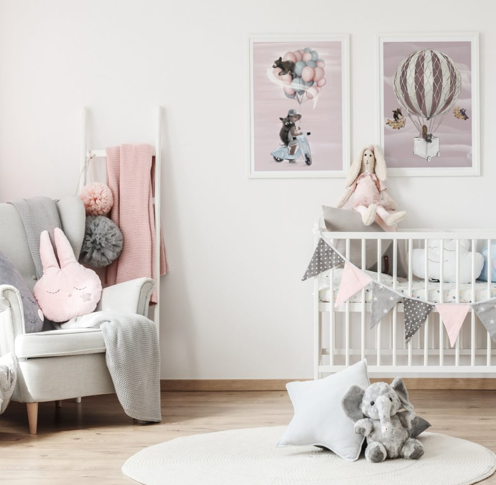 Light and pink coloured nursery with two Linn Wold wall prints on the wall