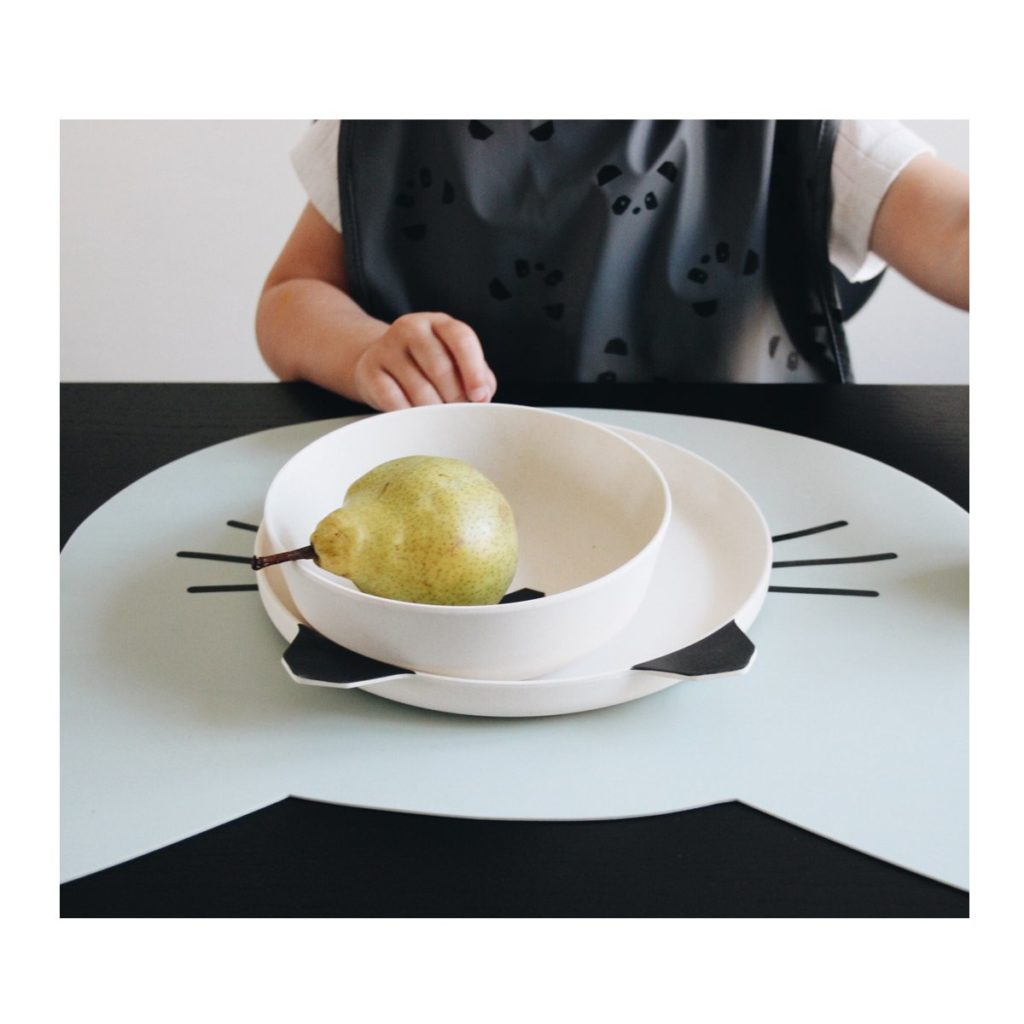 Bamboo plate set with a panda face and a pear in it