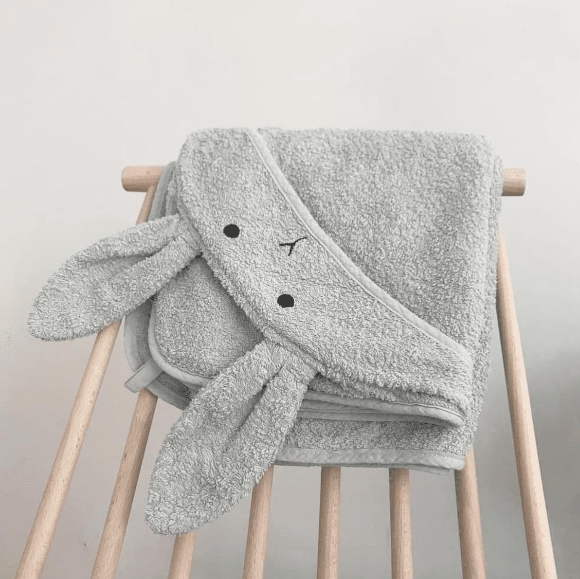 Dusty mint hooded baby towel folded on nursery chair