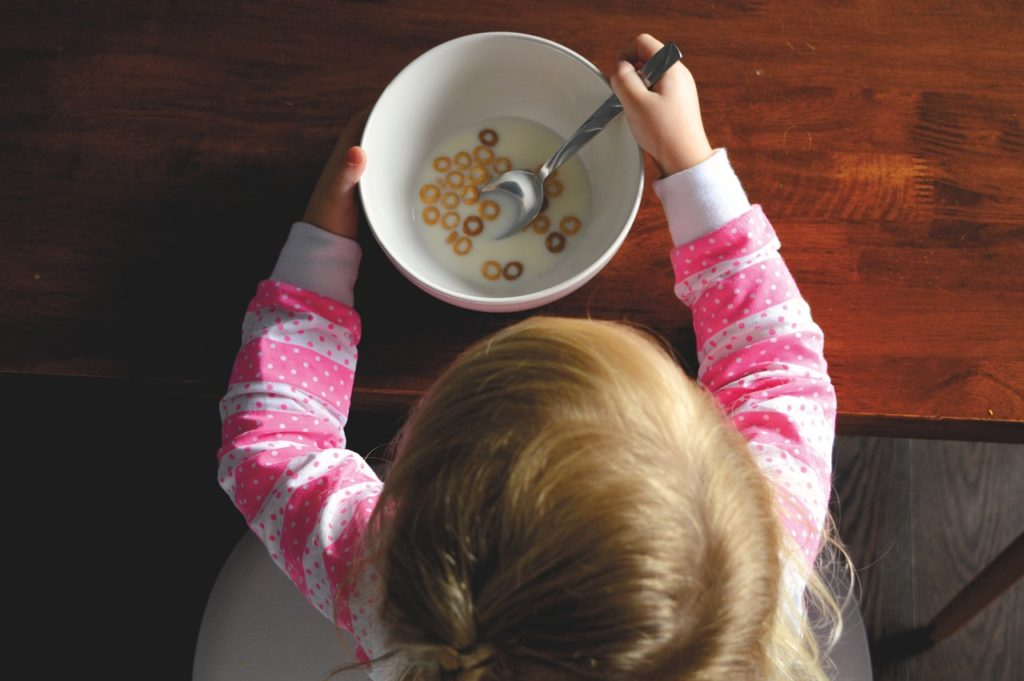 Child eating cereal at table