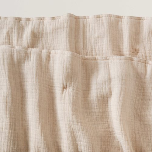 close up of corner of blush soft cotton filled muslin quilt blanket