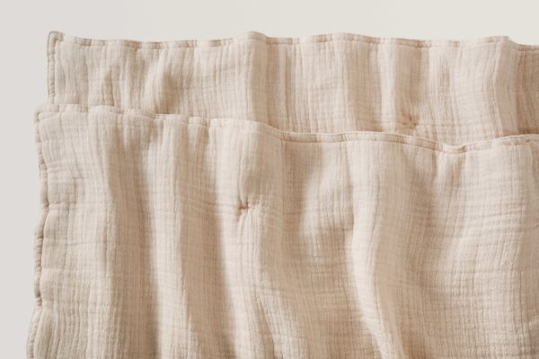 close up of corner of blush soft cotton filled muslin quilt blanket