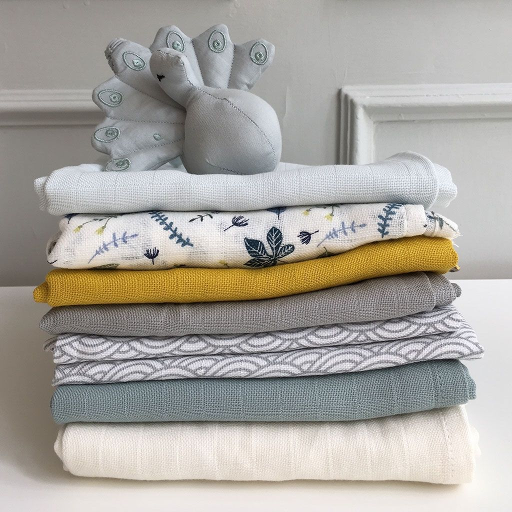 Pile of organic cotton muslins wraps and swaddles in mustard, grey, petroleum and other colours