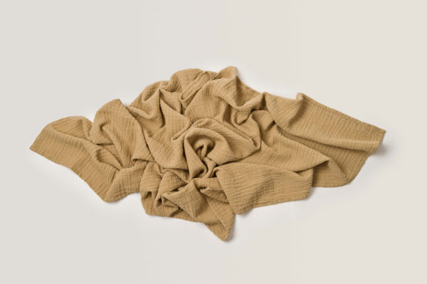 Baby swaddle wrap blanket in a pile beige