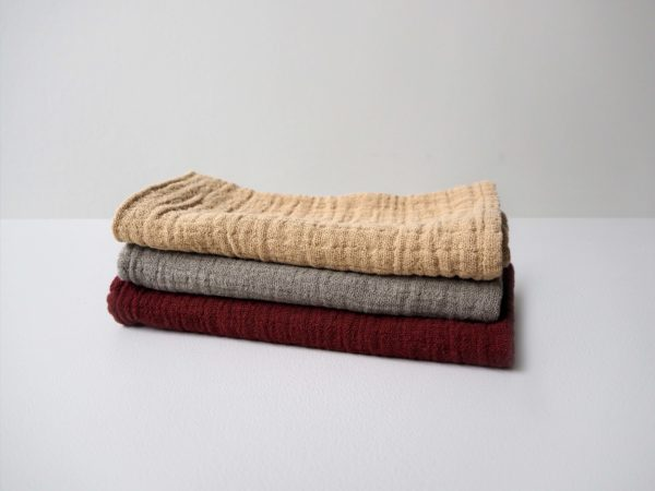 Three coloured soft cotton muslin swaddle blanket on top of each other