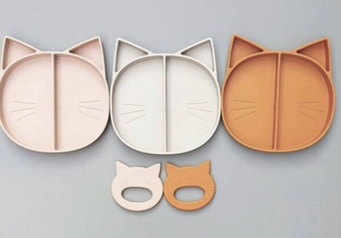 Three cat shaped silicone divided plates lined up with two cat shaped silicone baby teether underneath them