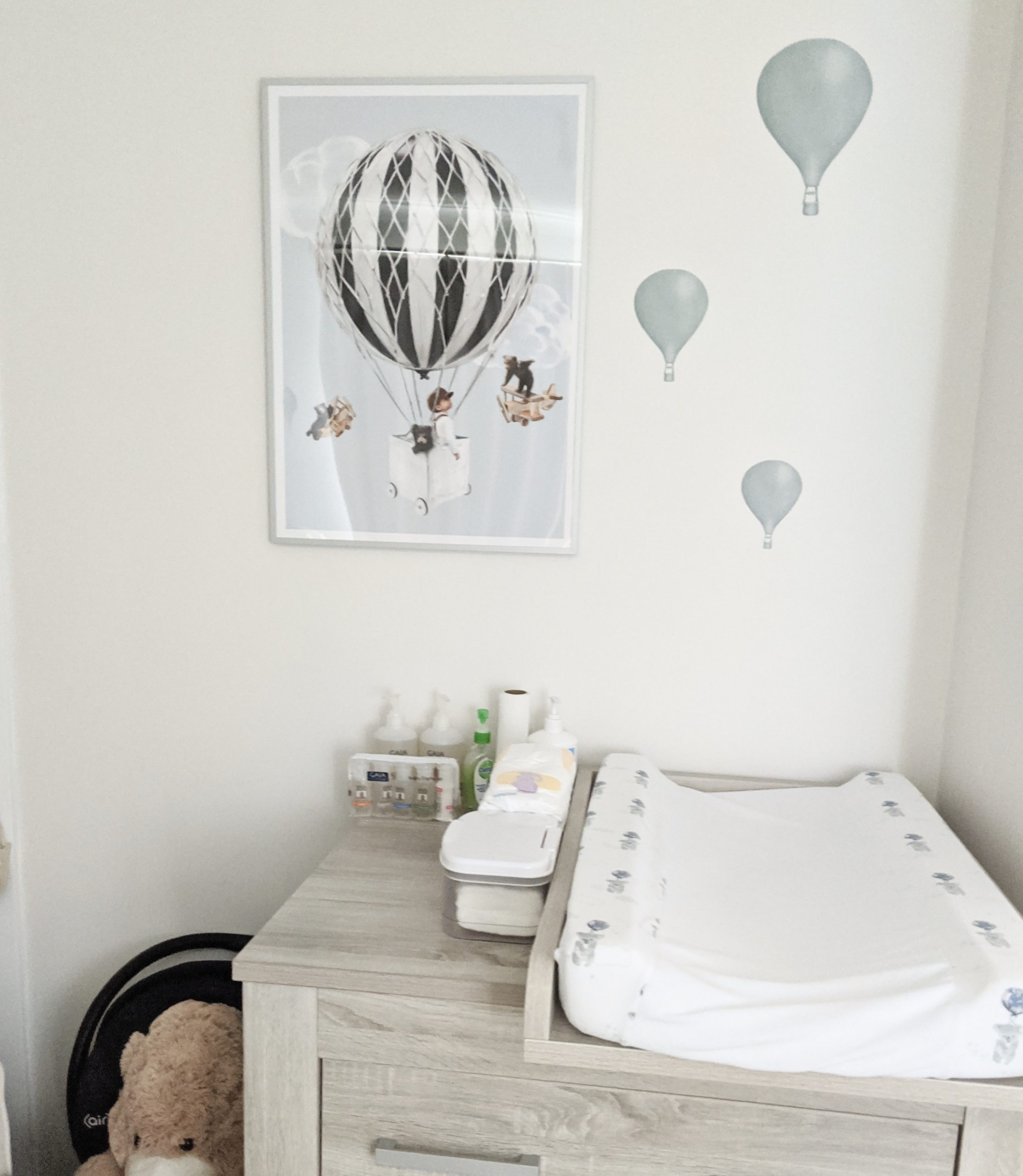 Changing table and changing mat on top with nursery wall print and light blue balloon wall stickers above it