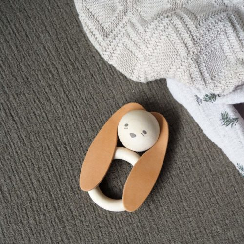 Baby bunny wooden teether lying on soft organic muslins and a baby blanket
