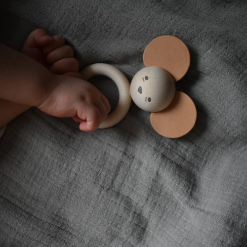 Baby's hand holding on to wooden mouse teether