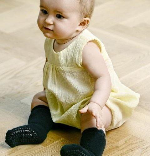 Toddler sitting on the floor wearing black organic cotton non slip socks