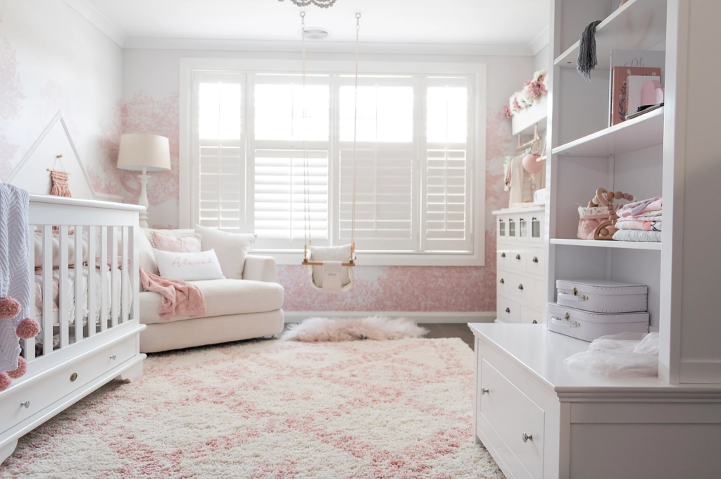 Pink and white nursery room with cot and shelving