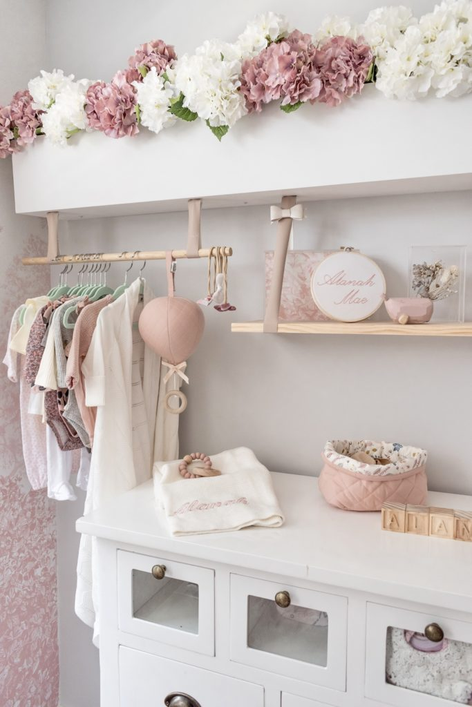 Baby nursery with white changing table, pink balloon music mobile, storage basket and wooden teething ring on display
